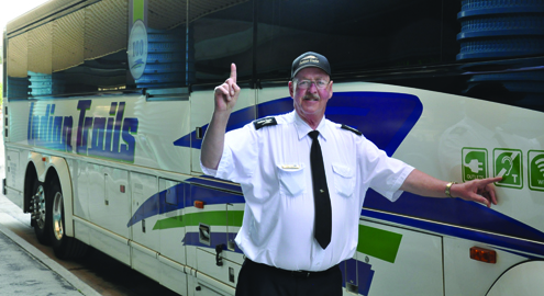 Ernie Nieman, an Indian Trails driver for 22 years, points to the icon indicating that his vehicle is part of the first bus fleet in the U.S. to be equipped with hearing loops.