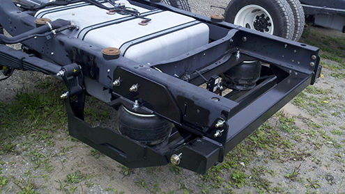 The two-stage suspension attaches to the back of the rear leaf springs shown on this Ford E450. The rear springs stay in place and maintain stability.