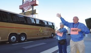 Clifford Boyer and Marge Sheldon hold signs of support during the motorcoach cruise.